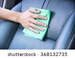 Hand cleaning the car interior with green microfiber cloth - stock photo