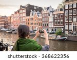 Stock photo beautiful young woman takes pictures in vacation spent in amsterdam with beautiful architecture 368622356