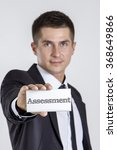 Small photo of Assessment - Young businessman holding a white card with text - vertical image