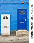 Small photo of Adjoining town houses with white and blue front doors