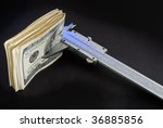 Close up of a pile of one hundred dollar bill been measured for a caliber - stock photo