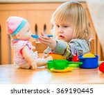Girl Feeding A Doll At Home In...