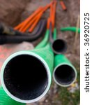 Close up of end of plastic pipe in a ditch - stock photo