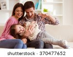 smiling young parents and their ... | Shutterstock . vector #370477652