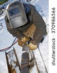 Small photo of Industrial worker uses an acetylene torch in winter outdoor
