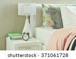 Stock photo clock and white table lamp next to striped bedding 371061728