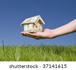 Man Holding A Dollar House...