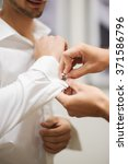 a groom fastening a cuff link... | Shutterstock . vector #371586796