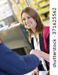 Small photo of Portrait of cashier with customer paying grocery products