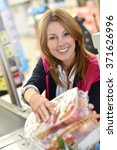 Small photo of Portrait of smiling cashier working in grocery store