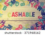 Small photo of cashable word block concept photo on plank wood