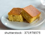 Stock photo two pieces of cornbread on a white plate 371978575