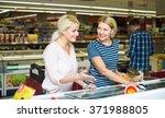 women choosing frozen meat in... | Shutterstock . vector #371988805