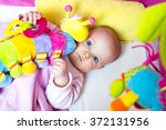 baby in bed with a colorful toy | Shutterstock . vector #372131956