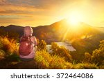 Stock photo woman with backpacker enjoying sunrise view at summit top in high mountain volcano rinjani island 372464086