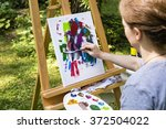 Woman Painting At A Canvas Wit...