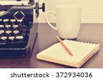 Small photo of blank notebook, cup and vintage typewriter on the writer's desk