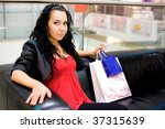 girl with bags sit on coach - stock photo