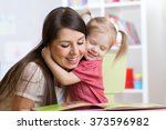 mother  embracing and reading ... | Shutterstock . vector #373596982