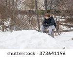Young boy sitting on a wooden fence holding a snowball - stock photo