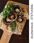 Small photo of Baked champignons with rosemary and onion rings abd parsley