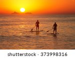 Young Men Paddle Surfing At...