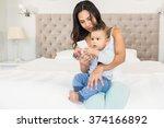 happy brunette holding her baby ... | Shutterstock . vector #374166892