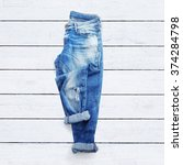 jeans on a white wooden... | Shutterstock . vector #374284798