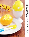Small photo of painting easter eggs with yellow color. in background egg with stars and twig of american witchhazel