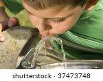 little boy drinking water from... | Shutterstock . vector #37473748