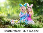 Small photo of Kids on Easter egg hunt in blooming spring garden. Children with bunny ears searching for colorful eggs in snow drop flower meadow. Toddler boy and preschooler girl in rabbit costume play outdoors.