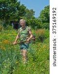a man weeds garden bed with hoe.... | Shutterstock . vector #375169192