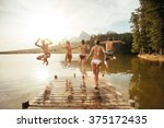 Rear view portrait of young friends jumping into a lake. Young people running and jumping from a jetty in to a lake on a sunny day. - stock photo