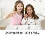 two young girls brushing teeth... | Shutterstock . vector #37557562