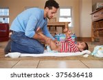 father changing son's diaper at ... | Shutterstock . vector #375636418