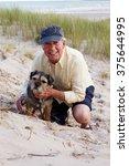 Stock photo portrait of senior man taking dog for walk on beach 375644995