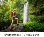 young woman backpacker looking at the waterfall in jungles.Ecotourism concept image travel girl