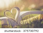 Small photo of Close up heart shape from paper book on grass field with vintage filter