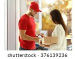 Small photo of Young woman receiving parcel from delivery man