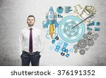 Small photo of A man with hands in pockets, a picture of a target surrounded by pictures of money, rocket, charts, cogwheels and puzzles painted to the right. Concrete background. Concept of achieving a set goal.