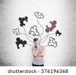 Stock photo a man standing with a hand on his chin at a concrete wall with parts of a puzzle drawn on it front 376196368