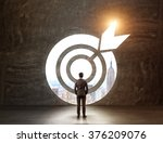 Small photo of A businessman with hands in pockeys standing in front of a target through which he can see New York. Back view. Black background. Concept of achieving a goal.