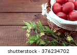 Basket with red easter eggs on rustic wooden table.