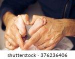 newborn baby feet on male hands ... | Shutterstock . vector #376236406