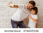 Small photo of Handsome young father making a photo with his cute little son. A little boy showing OK sign. Both in white t-shirts smiling, standing against white brick wall.