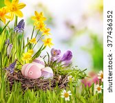 Small photo of Colorful Easter greeting card with a cluster of decorated eggs in a nest amidst fresh green grass and spring flowers with copy space in square format