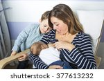 a young mother feeding her... | Shutterstock . vector #377613232