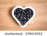 black beans in the heart shape block on the wood background