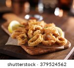 fried calamari rings on wooden... | Shutterstock . vector #379524562