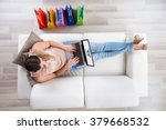 young woman sitting on sofa... | Shutterstock . vector #379668532